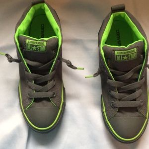 Grey trim in green converse tennis shoe.
